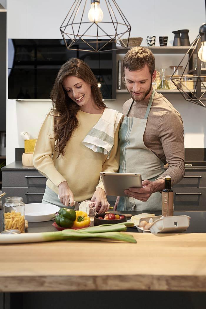 Un jeune couple qui prépare son repas avec des légumes racines