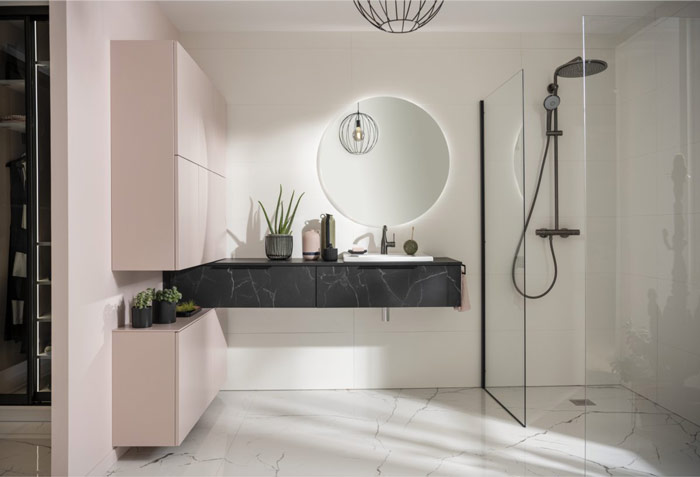 salle de bains rose et plan de toilette marbre noir