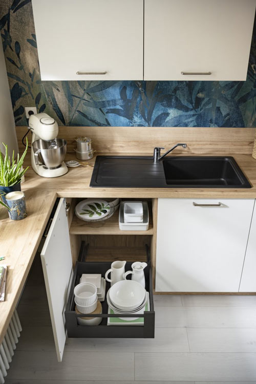 Petite cuisine en « L » fermée avec des murs en papier peint motif végétal bleu