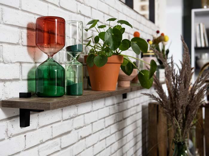 Sablier et plante posés sur une étagère bois